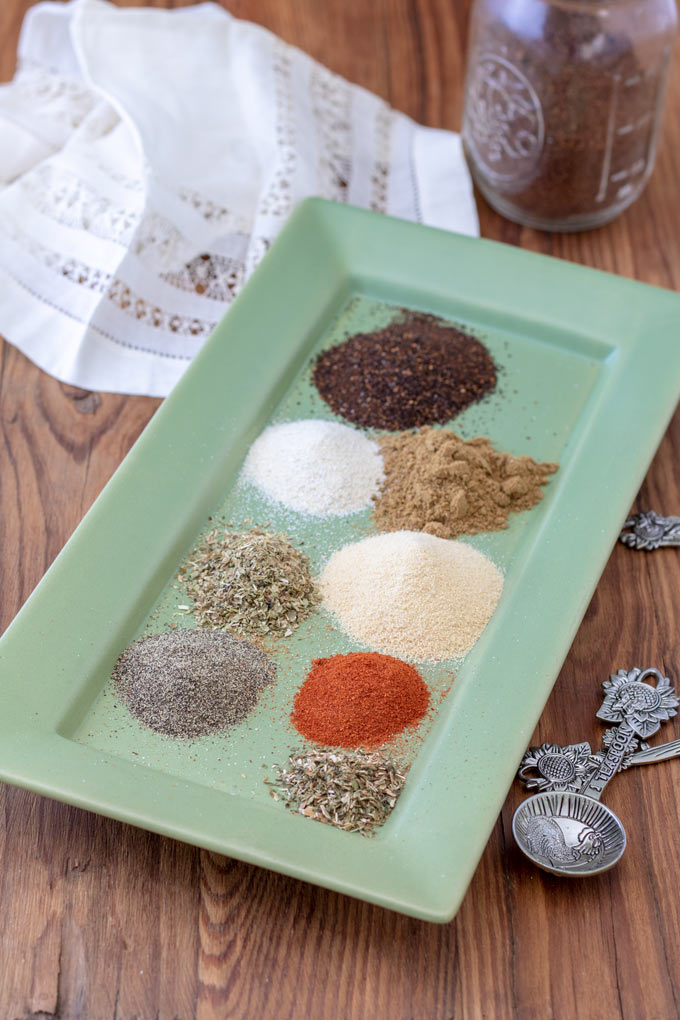 ingredients for taco seasoning with plate with wooden background