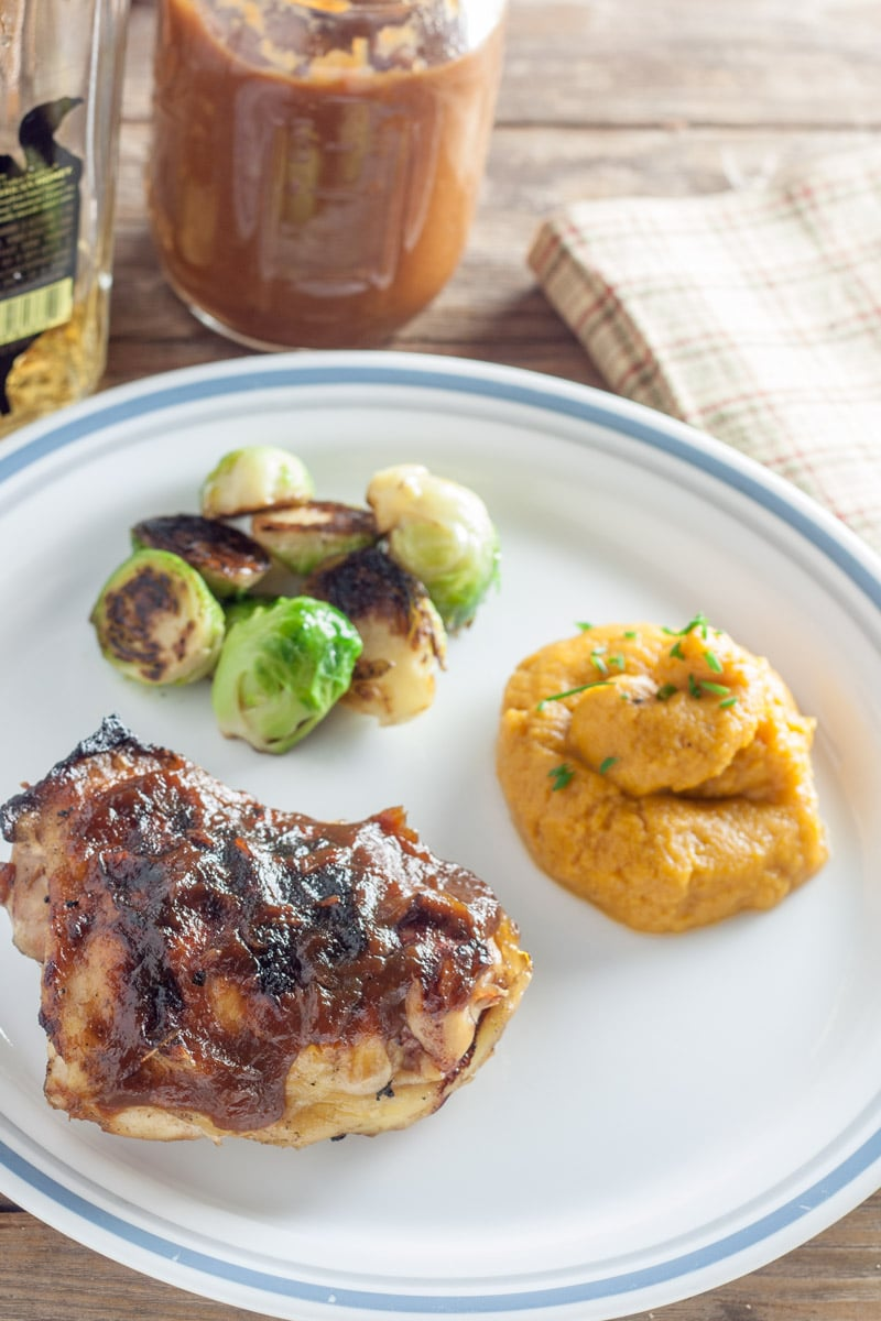 chicken thigh grilled with peach bourbon BBQ sauce with roasted brussels sprouts and rustic beige napkin