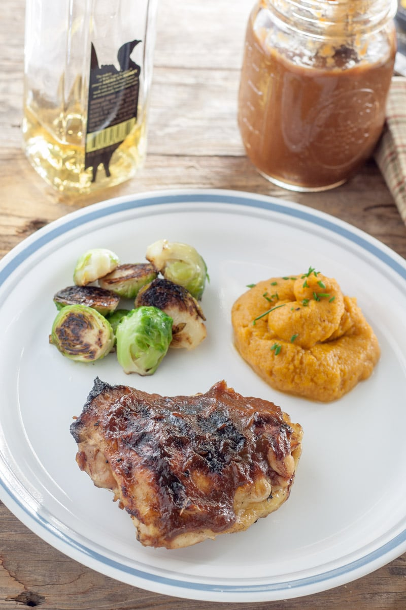 Chicken thigh grilled with peach bourbon BBQ sauce with side dishes of sweet potato puree and roasted brussels sprouts.