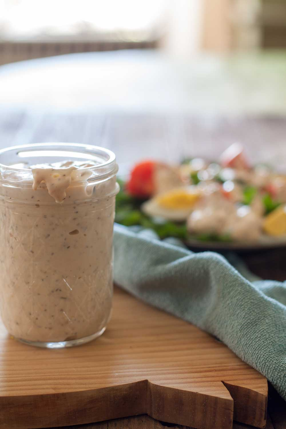 thousand island dressing in half pint jar on wooden board with blue napkin
