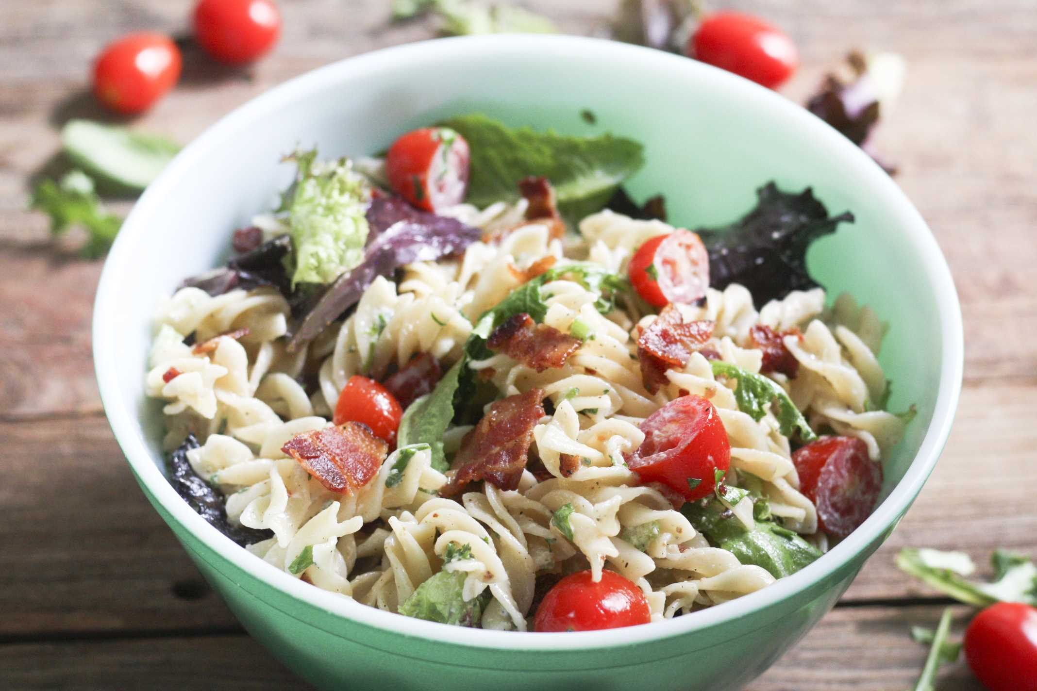 BLT Pasta Salad in green bowl with chunks of bacon on top