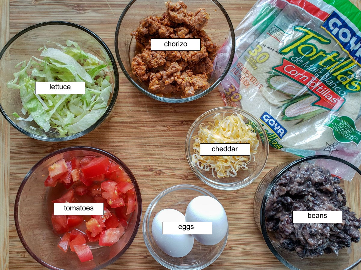 Ingredients, chorizo, tortillas, lettuce, tomatoes, cheese, eggs, beans.