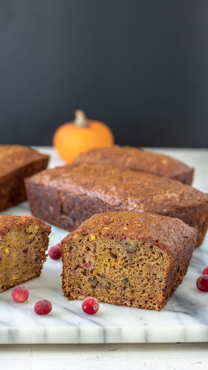 Cut pumpkin quick bread with chunks of cranberry and orange.