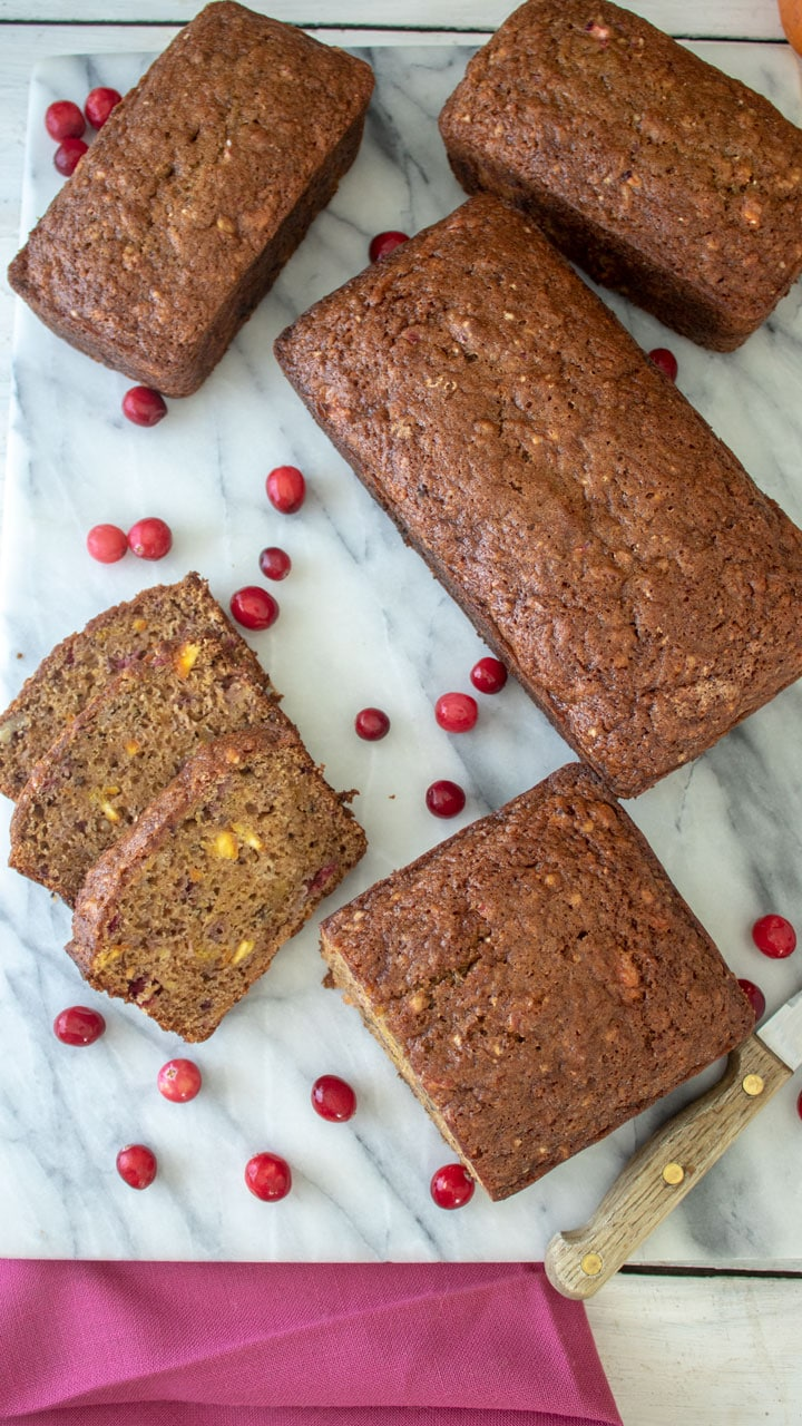Slices of Orange Cranberry Pumpkin Quick Bread next to whole loaves