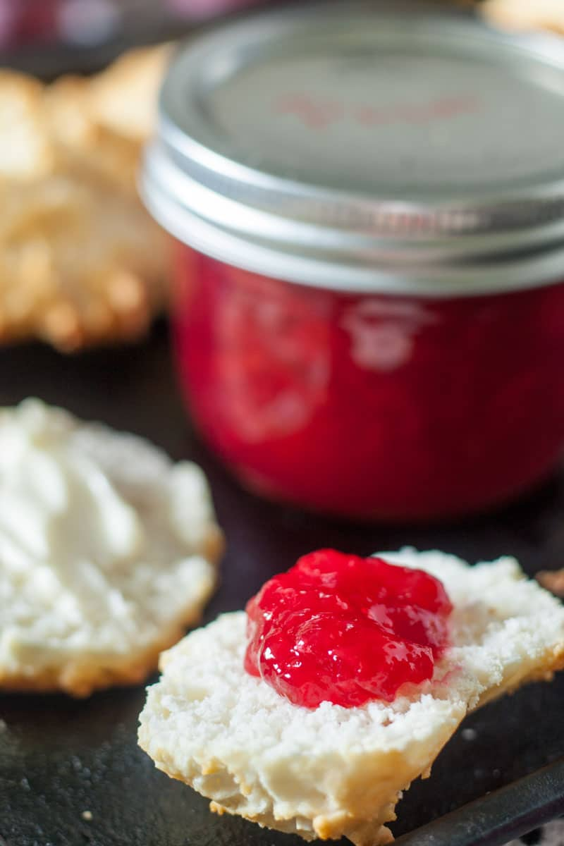 plum jam on metal baking tray with biscuits and jar of jam