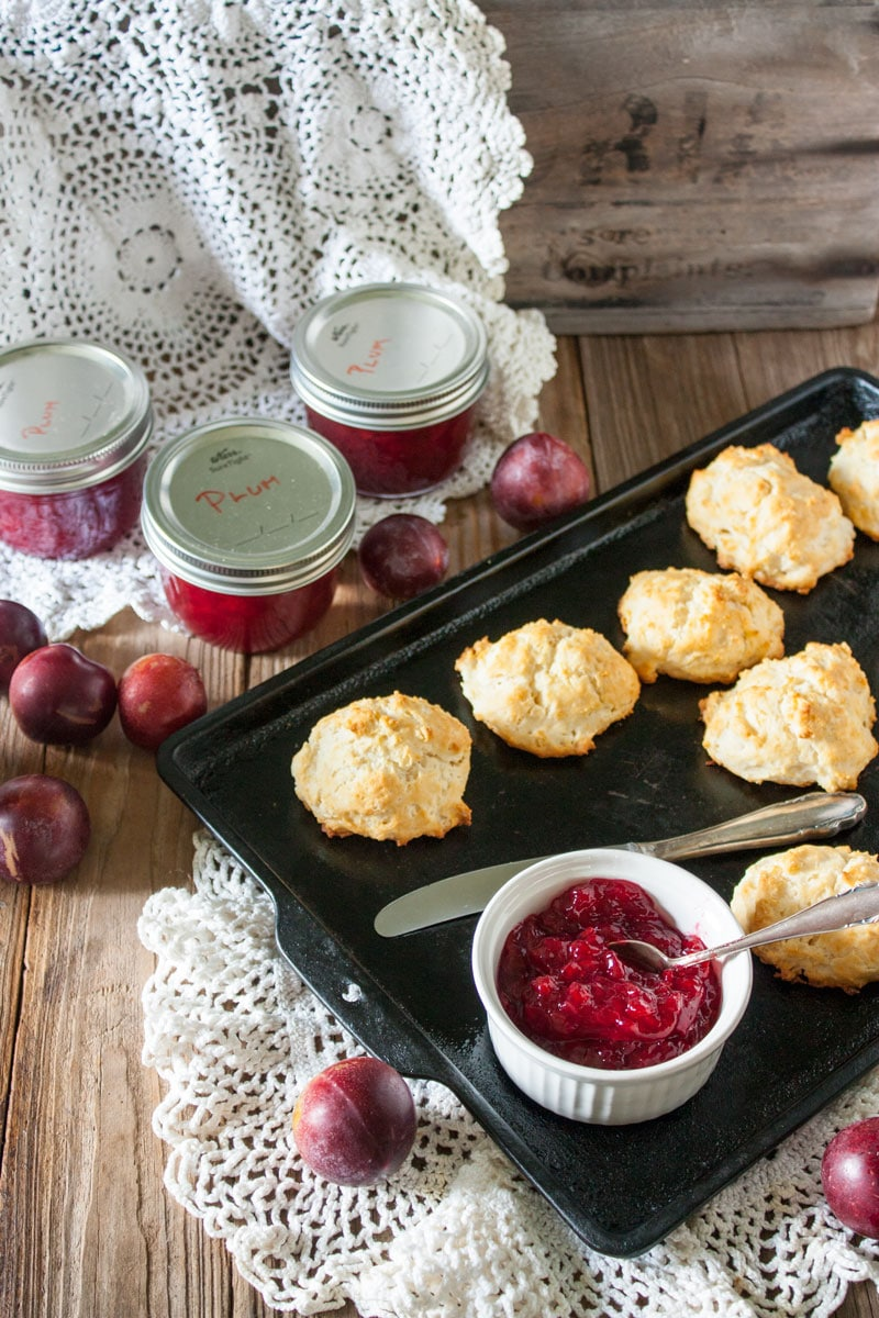 plum jam in white bowl on antiques baking sheet with biscuits and antique doily