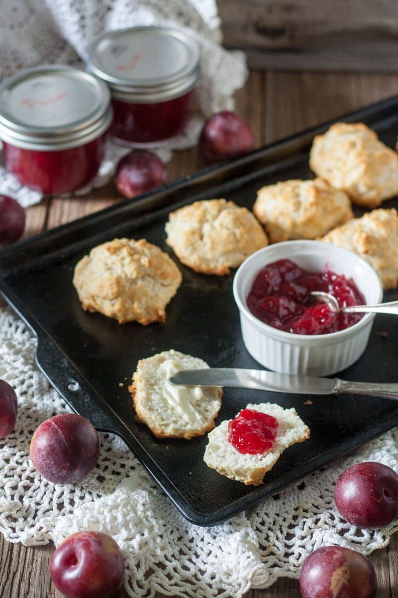 plum jam in white ramekin and butter and plum jam on biscuit