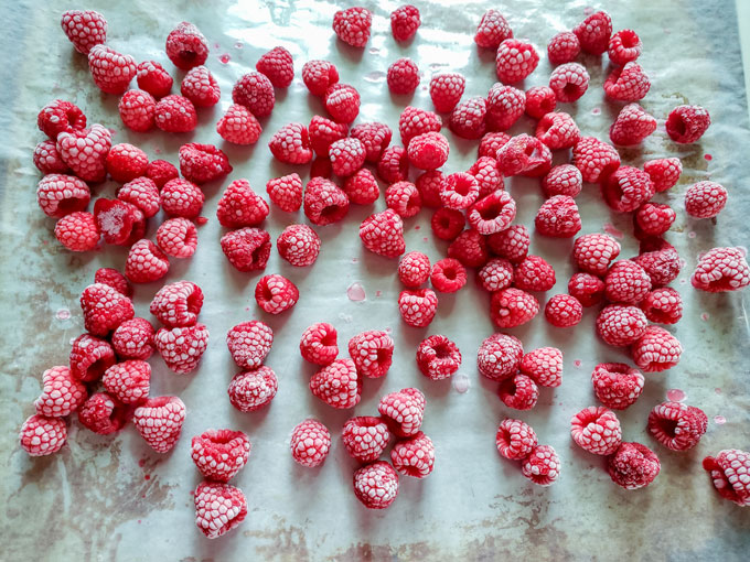 Frozen raspberries on sheet.