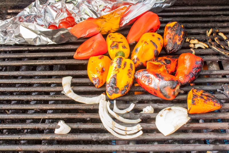 peppers, onions and tomatoes on the grill