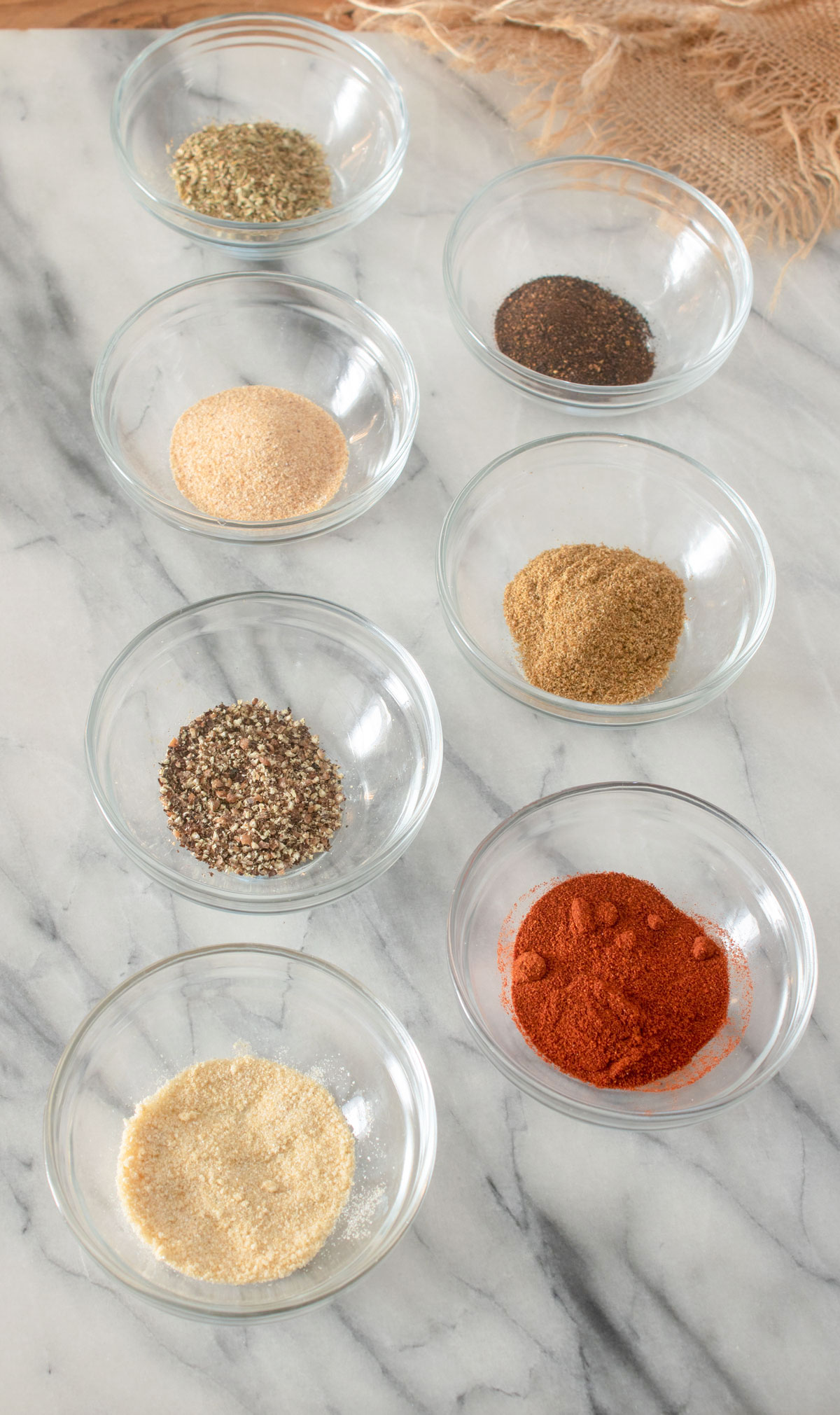 Spices in individual piles on marble board.