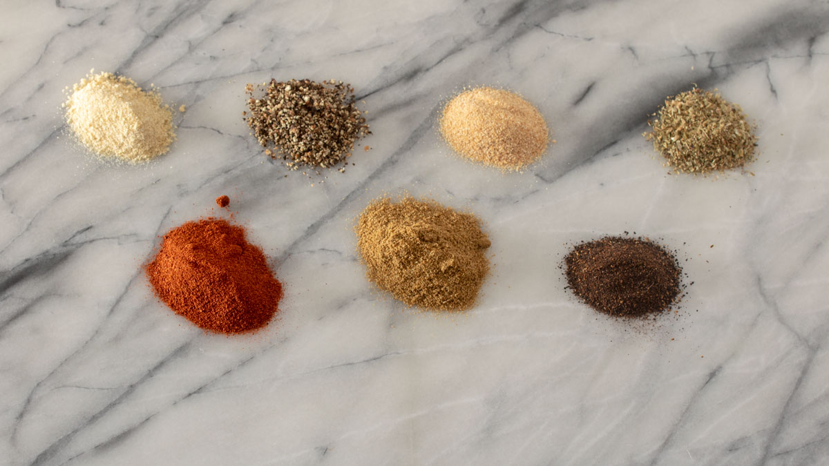 Spices in individual bowls on marble board.