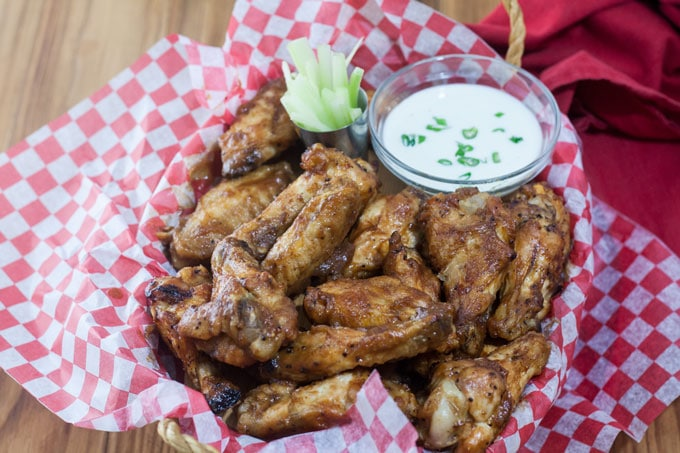 Chicken wings in basket with dipping sauce and celery.