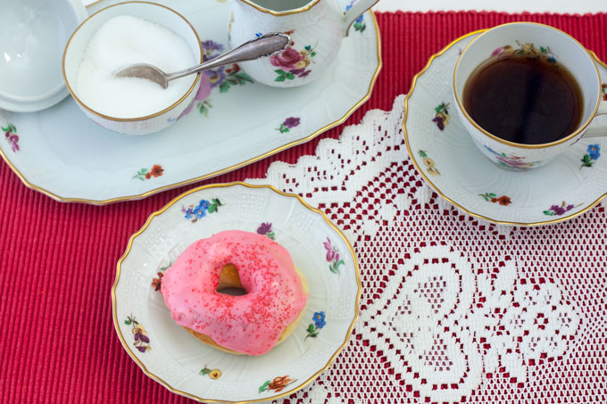 pink frosted doughnut on antique, flowered china plate