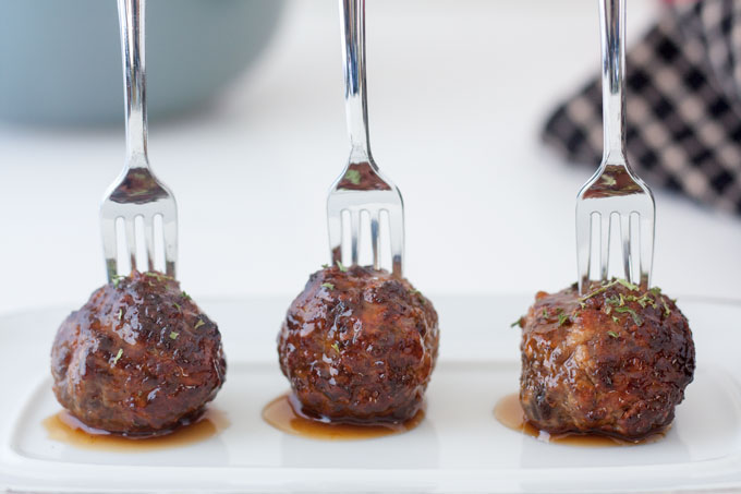meatballs on white plate with bowl of meatballs in background