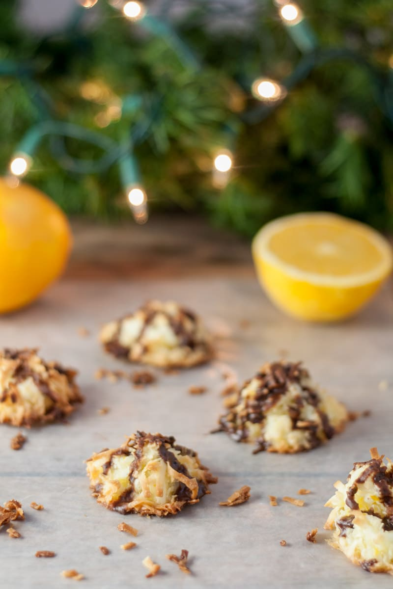 Chocolate drizzled coconut ambrosia macaroons on white paper with oranges