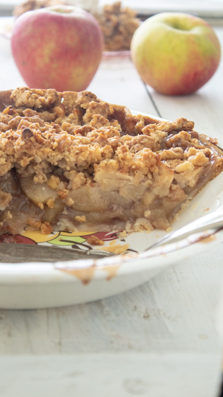 Inside of Apple crumb pie with apples in the background.
