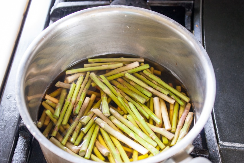 large ends of asparagus stalks in stock pot with water