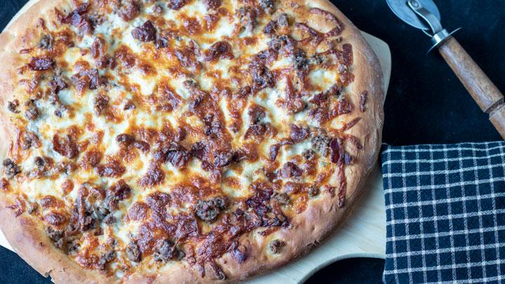 Whole pizza on pizza peel.
