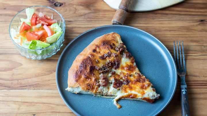 slice of pizza with side salad.