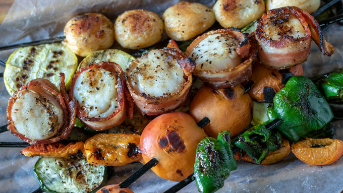 bacon wrapped scallops on bamboo basket with colorful veges