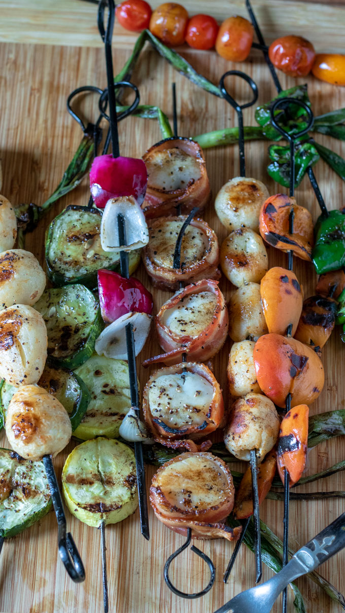 scallops on white plate with grilled vegetables