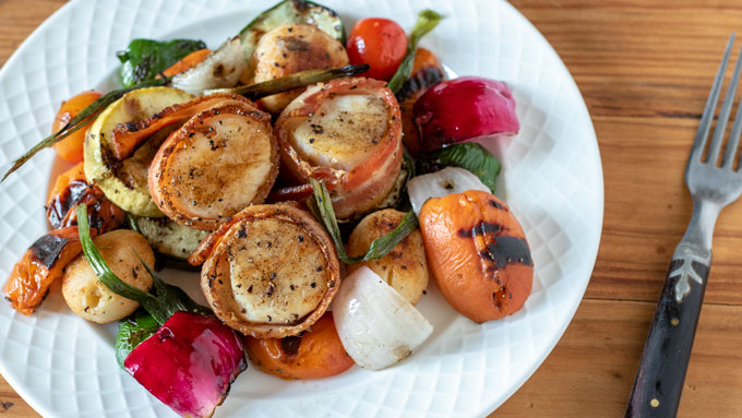 vegetables and bacon wrapped scallops on white plate
