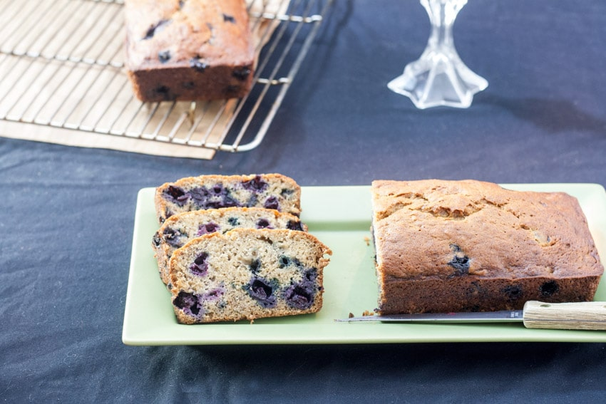 3 slices banana blueberry quick bread next to cut loaf oh rectangular light green plate