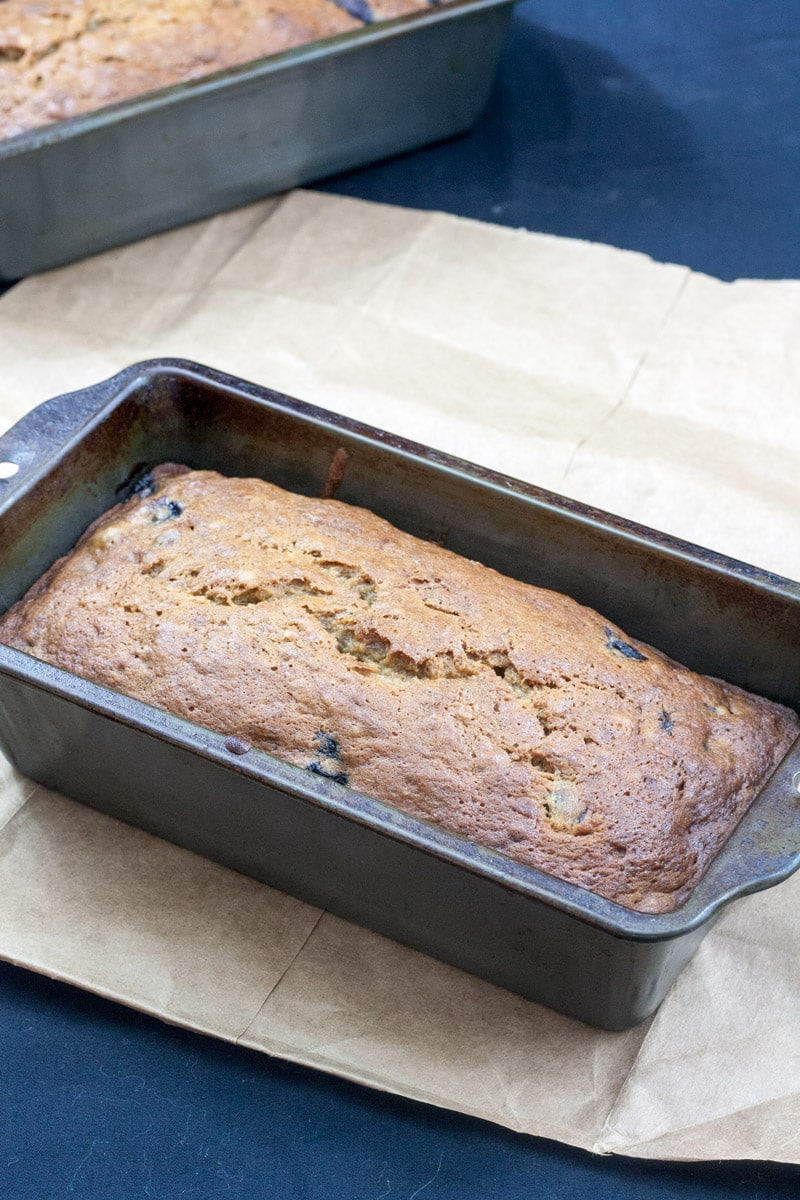 banana blueberry bread in metal loaf pan on brown paper
