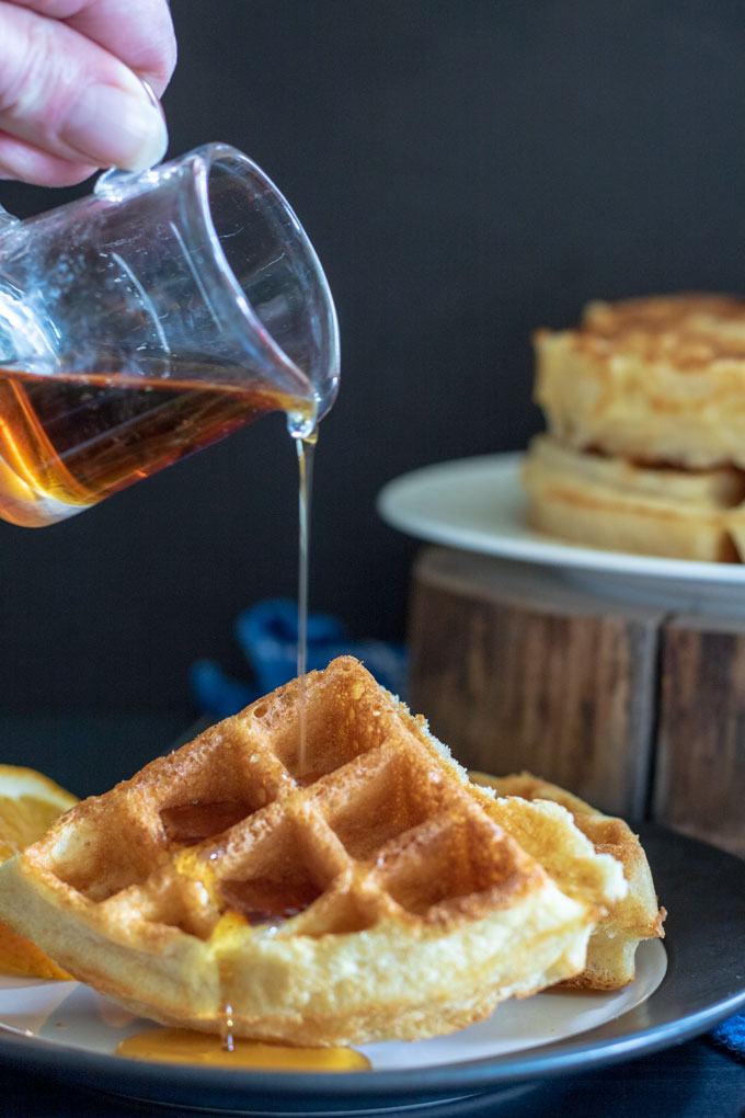 hand pouring syrup from pitcher onto belgian waffles