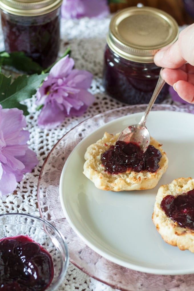 spreading blackberry jam on English muffin