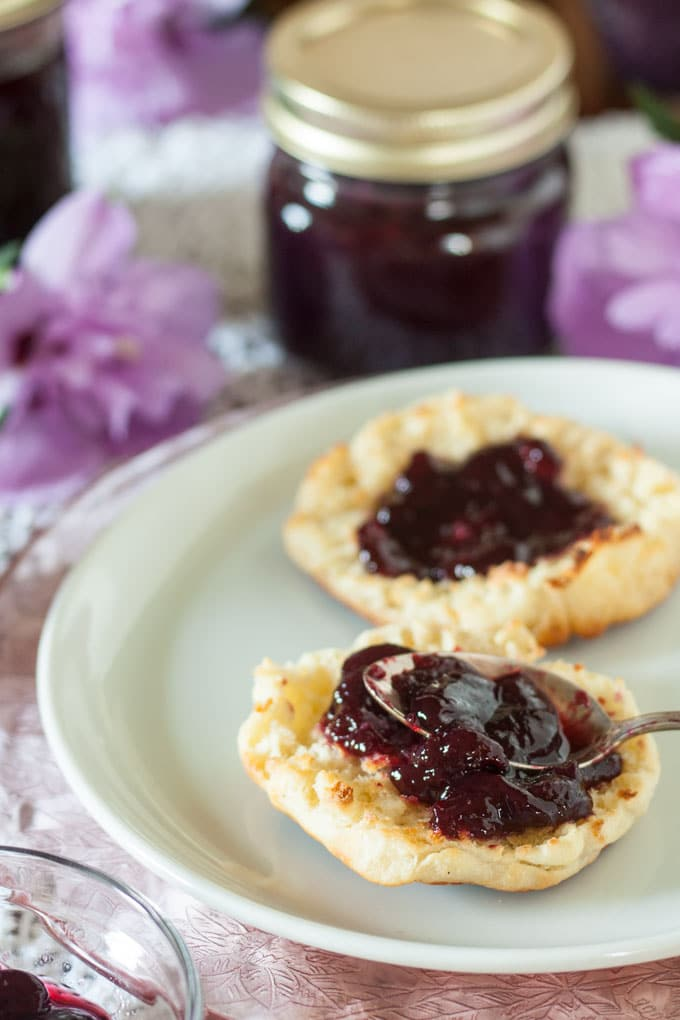 spooning blackberry jam on English muffin