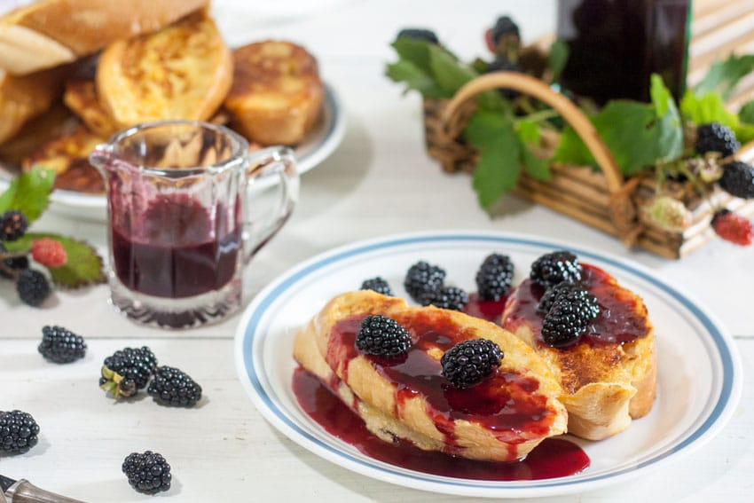 White plate with french toast topped with blackberry syrup and fresh blackberries