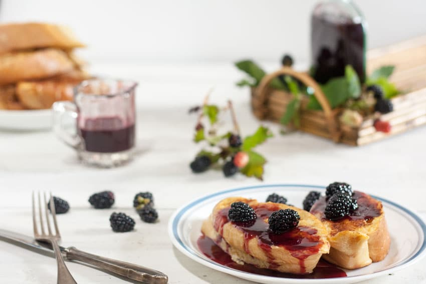 french toast on white plate dousied with blackberry syrup