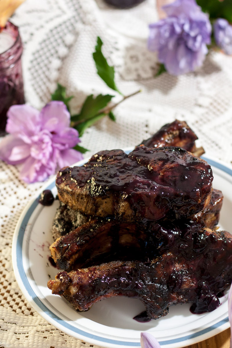 pile of pork ribs smothered in blueberry bbq sauce on white plate with purple flowers in background