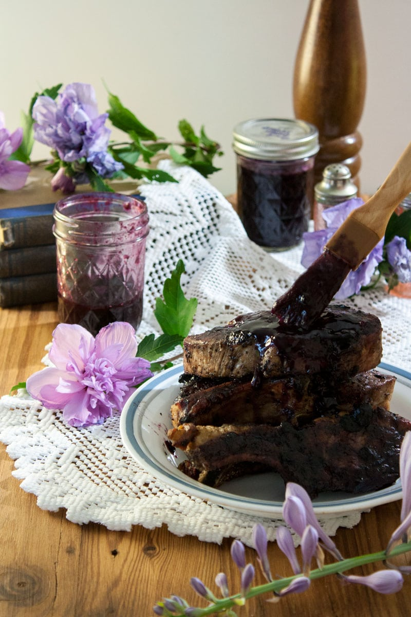 wooden brush brushing blueberry bbq sauce on ribs