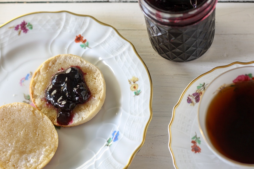 biscuit slathered with blueberry jam on antique white flowered plate