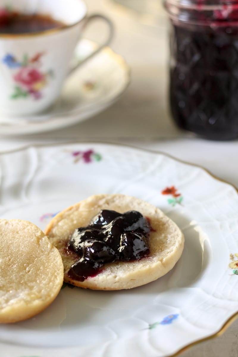 a biscuit with blueberry and tea cup