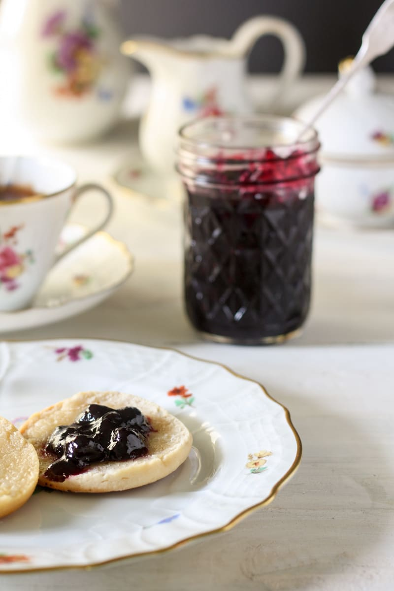 blueberry jam on biscuit on white plate with colored flowers