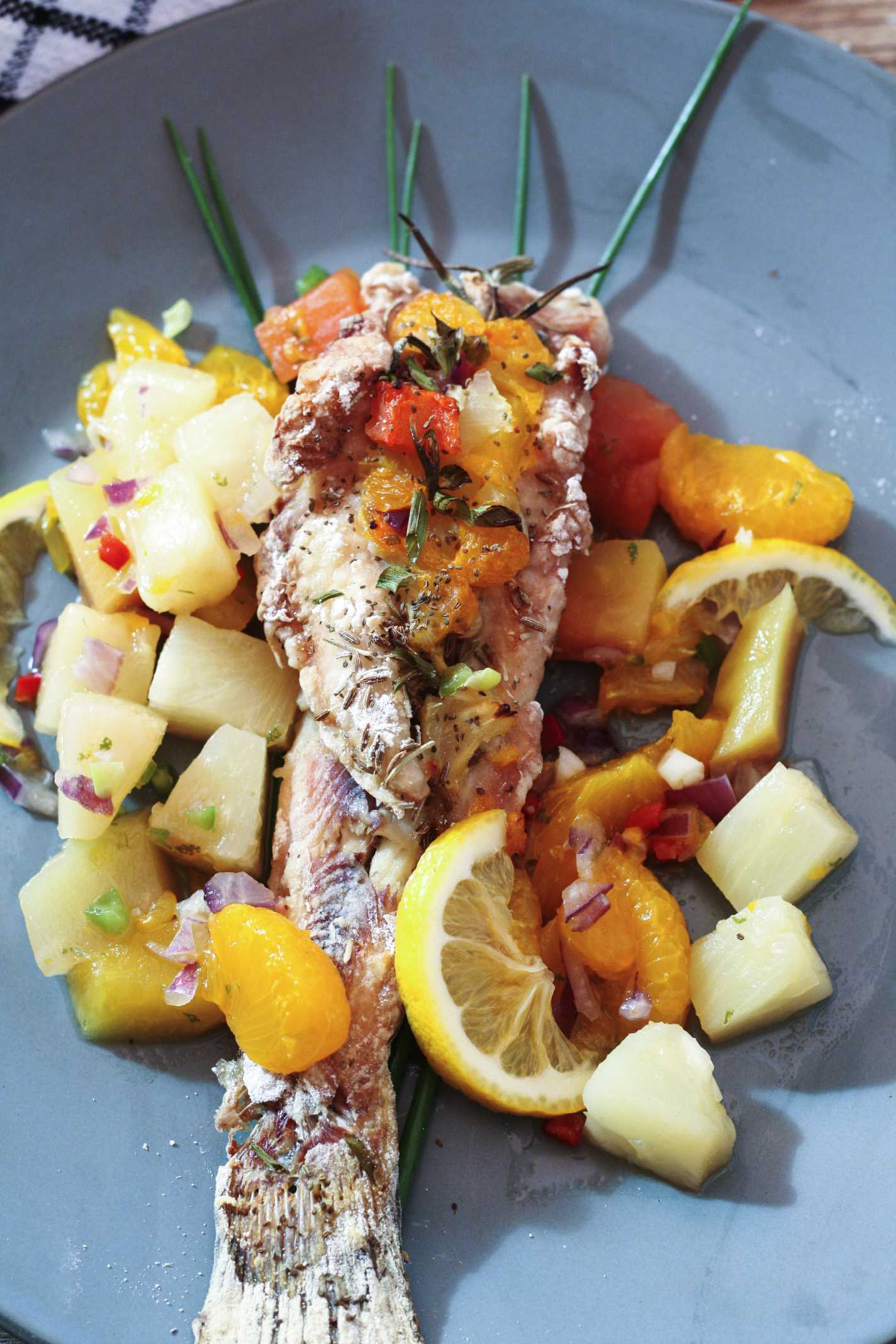 baked Bullhead on green plate surrounded by colorful citrus salsa