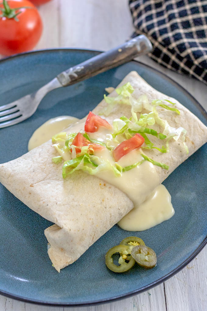 Burrito with cheese sauce garnished with tomatoes and lettuce