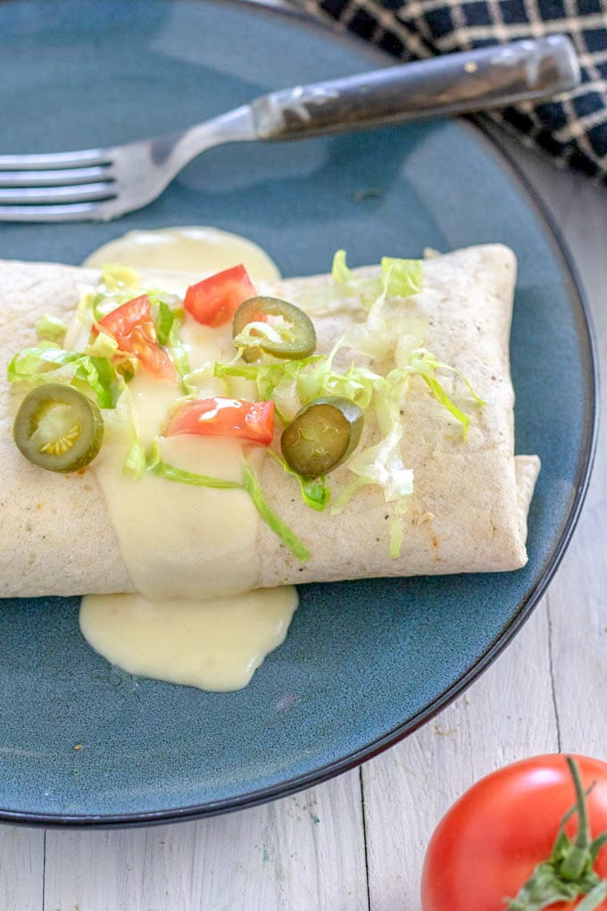 cheese sauce on burrito garnished with jalapeno pepper slices