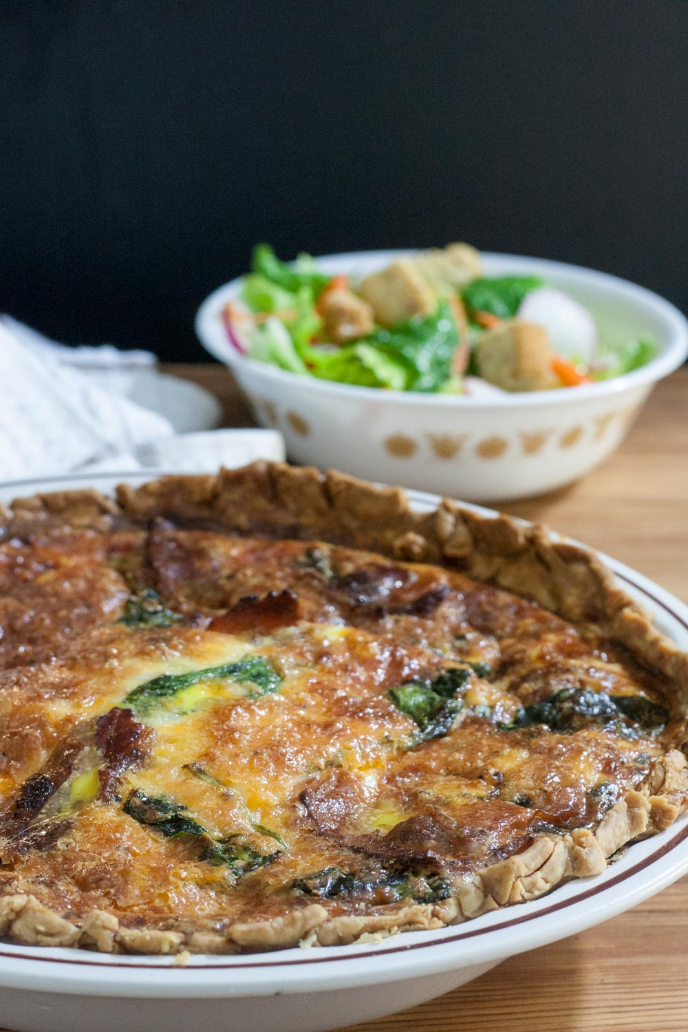 close up of whole quiche with spinach, chicken, bacon and cheese