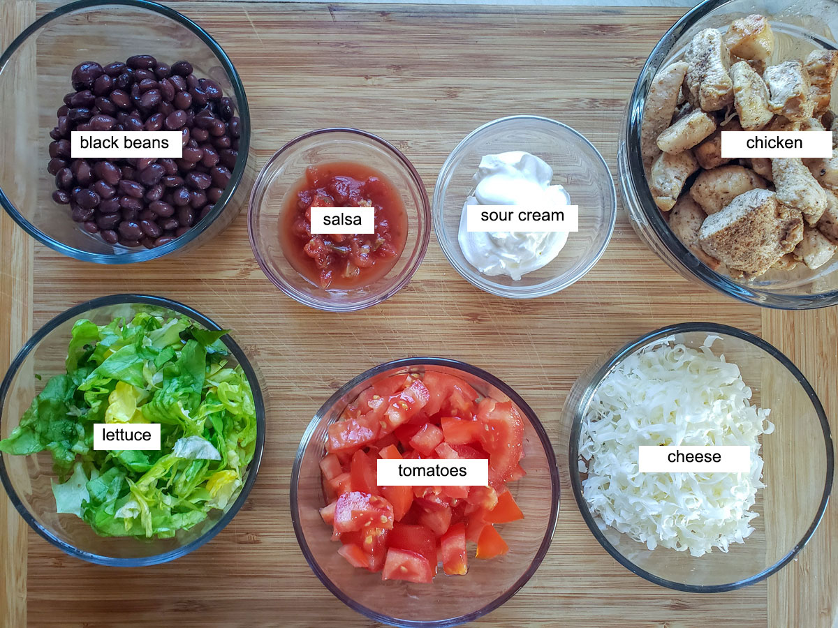 Ingredients for chicken nachos, Chicken, beans, lettuce, tomato, cheese on bamboo board.