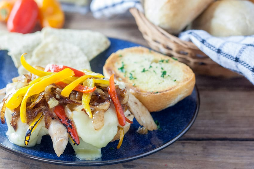 Open faced chicken cheese steak sandwich on blue plate with sauteed onions and colored peppers.