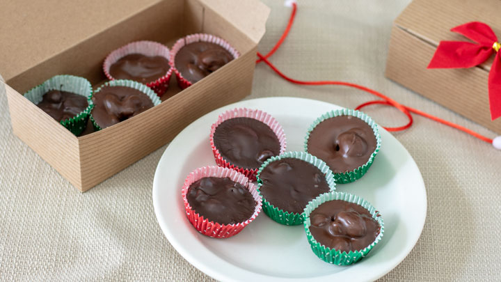 Chocolate covered nuts on white plate and in gift box.