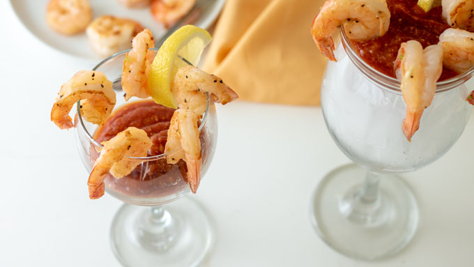 2 glasses with homemade cocktail sauce and shrimp cocktail