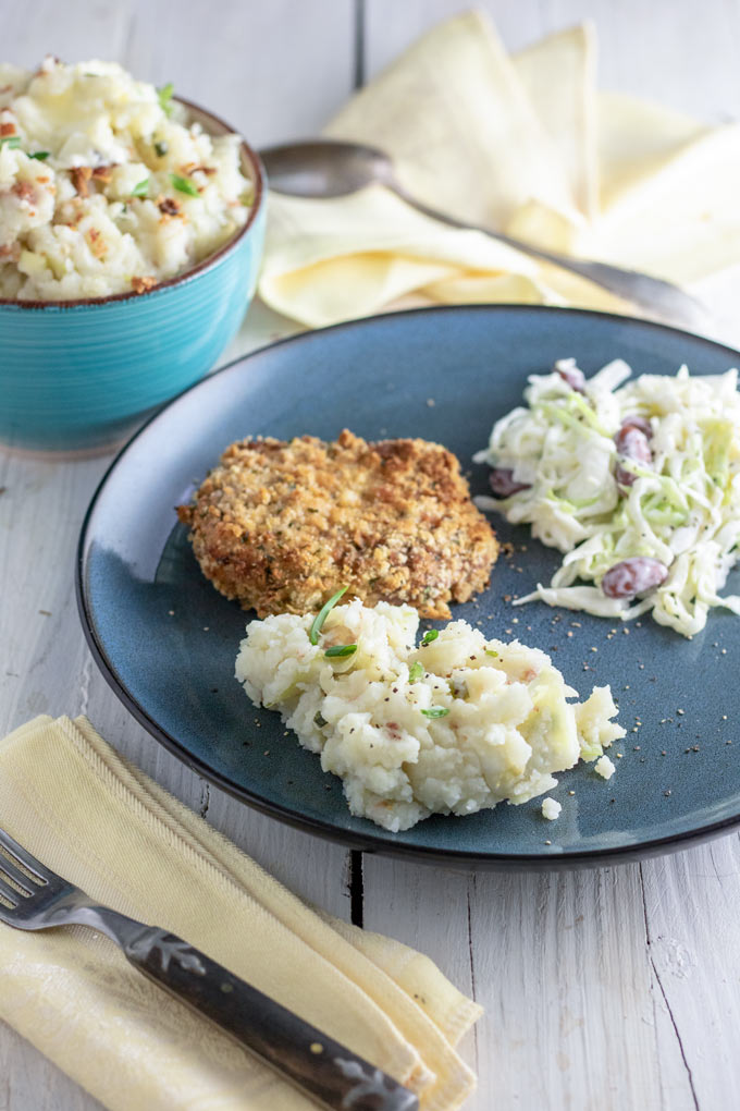 colcannon served with breaded pork chop and coleslaw on blue plate