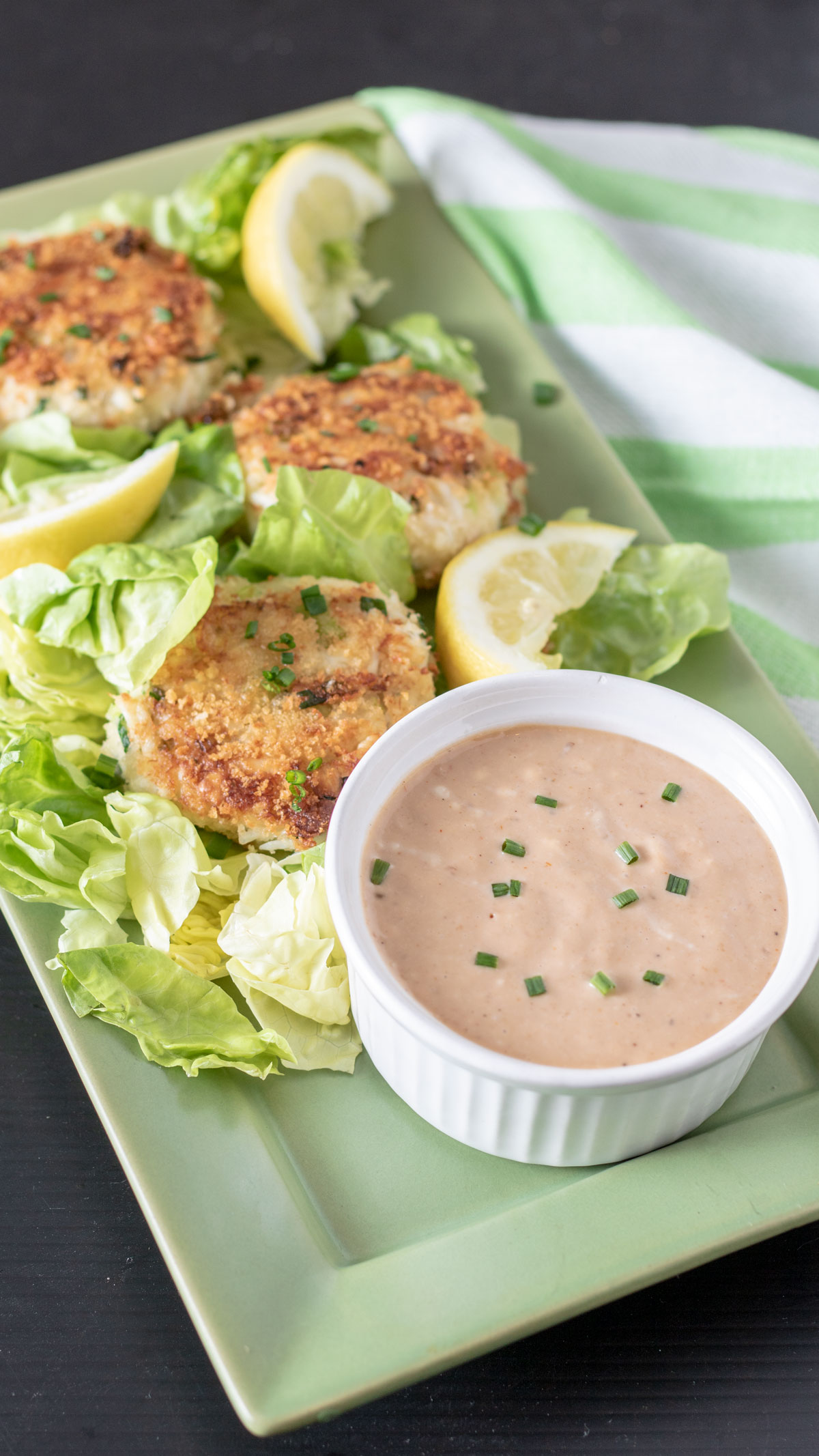 Serving tray with crab cakes and sauce garnished with lettuce leaves.