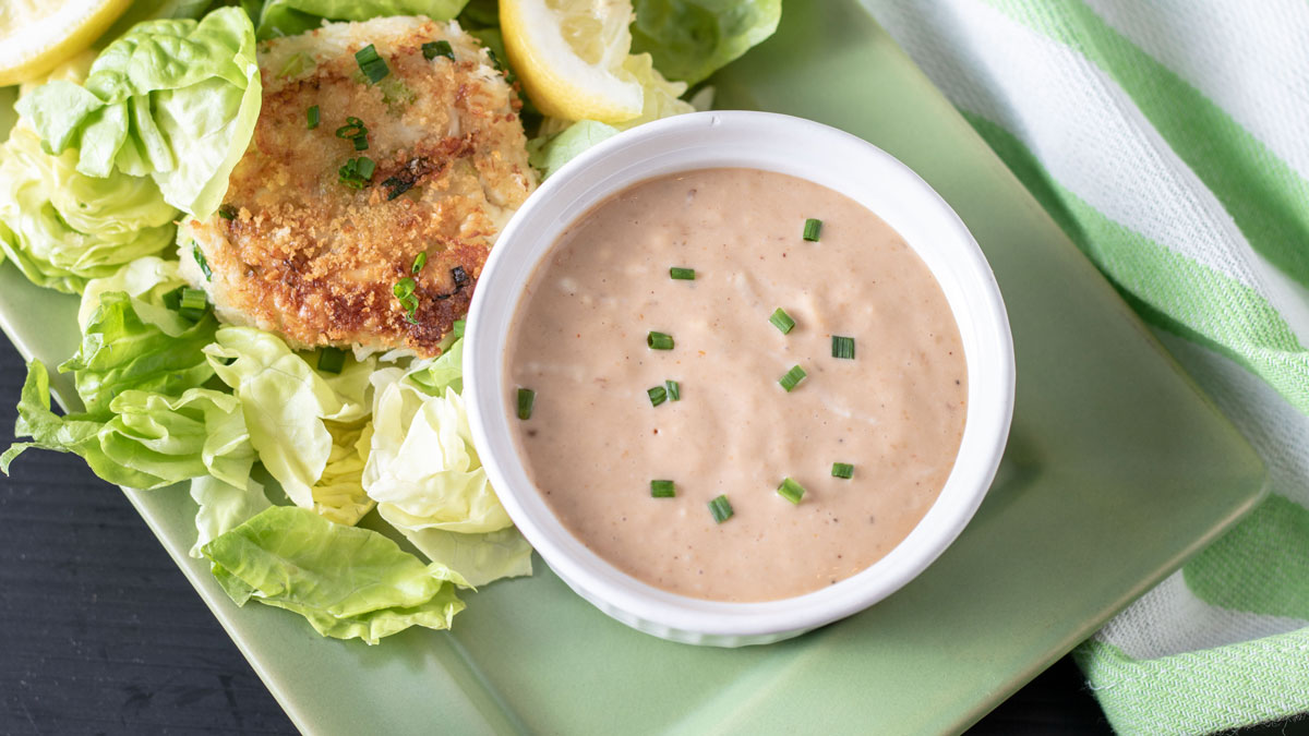 Comeback sauce in small white bowl with crab cakes.