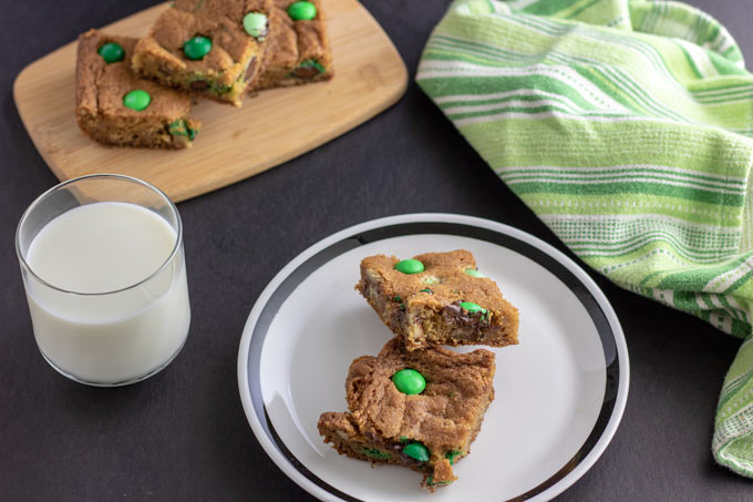 two cookie bars on white plate with milk
